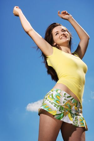 A beautiful young woman throwing her arms up in joy in front of a blue sky in the sunshine.