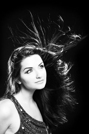 film noir: A black and white image of a beautiful young woman with flowing hair. Film noir style. Stock Photo
