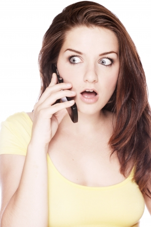 suprise: A beautiful young woman on her mobile pulling a shocked face.