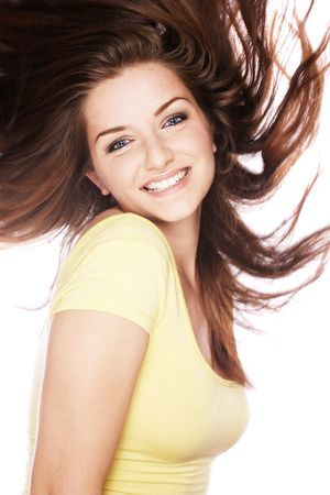 A beautiful young smiling woman lookin gat the camera with her hair in movement, on a white background. photo