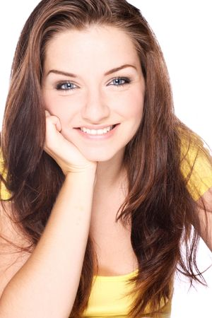 A beautiful smiling youing woman resting her head on her hand in front of a white background. photo