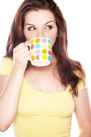 A beautiful young brunette drinking from a mug and looking to the side. Stock Photo - 5579436