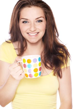 A beautiful young smiling woman holding a spotted mug. Stock Photo - 5576660