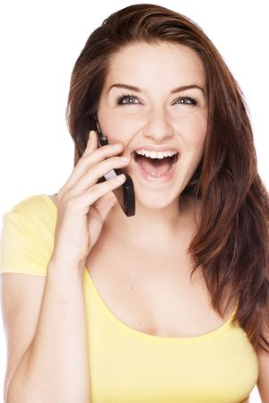 A beautiful young woman on her mobile phone and laughing on a white background. photo