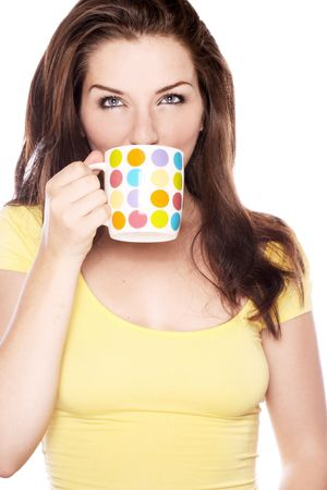 A beautiful young woman drinking from a spotty mug on a white background. Stock Photo - 5583356
