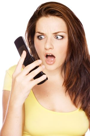 A beautiful young woman looking at her mobile with a shocked face on a white background. photo