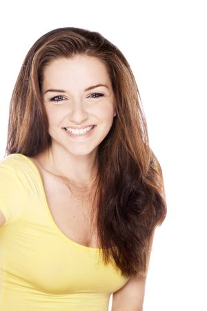 A beautiful young woman smiling in front of a white background. Copy space. photo