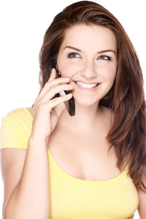 A beautiful young woman smiling while on her mobile phone, on a white background. photo