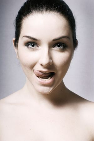 A beautifoul young woman pulling a funny face on a gray background. photo