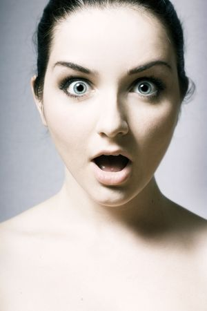 A beautiful young woman pulling a shocked face on a grey background. photo