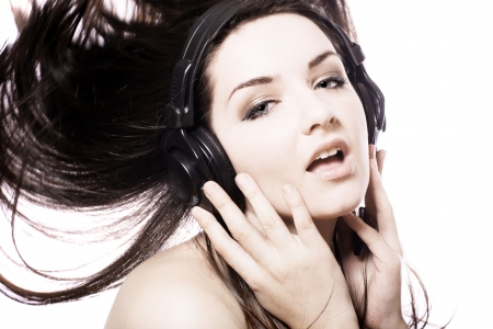 A beautiful young girl dancing and wearing headphones on a white background. Copy space. photo