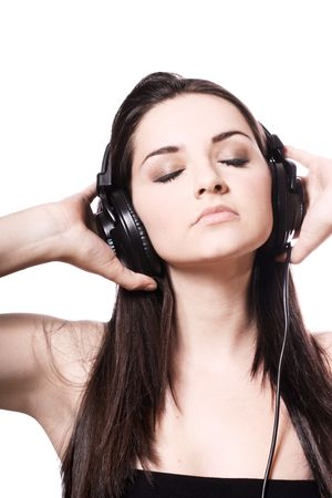 A beautiful young girl wearing headphones on a white background. Copy space above. photo