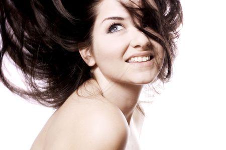 Una donna giovane e bella sorridendo e guardando al lato con i capelli in movimento su uno sfondo bianco.