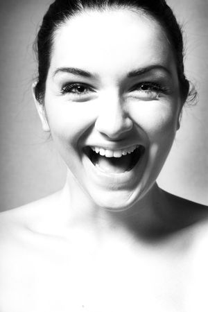 A Black and white close up of a happy woman laughing/smiling in front of a gray background.