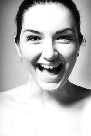 Un bianco e nero nei pressi di una donna felice ridere  sorridere di fronte a uno sfondo grigio. Archivio Fotografico