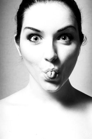 Una immagine in bianco e nero di una giovane donna che tira una faccia buffa di laminazione la lingua.