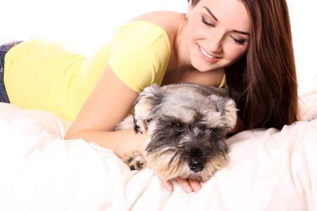 A pretty young woman in bed with her Miniature Schnauzer. photo