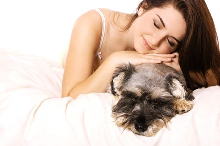 A pretty young smiling woman in bed with her Miniature Schnauzer. photo