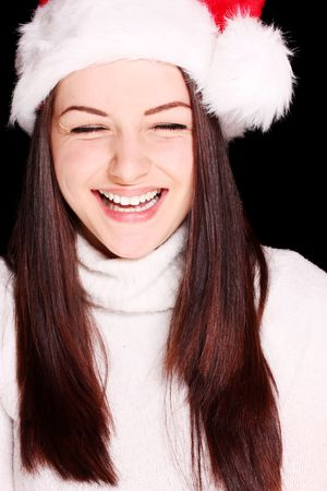 A pretty young woman wearing a santa hat on a black background. photo
