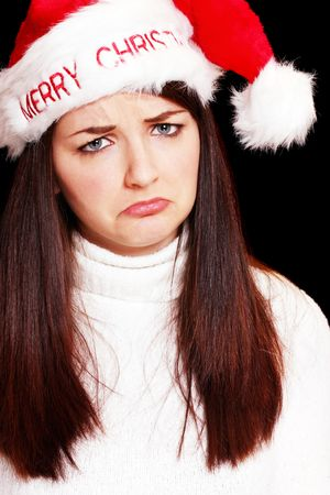 A sad young woman wearing christmas hat in front of a black background.