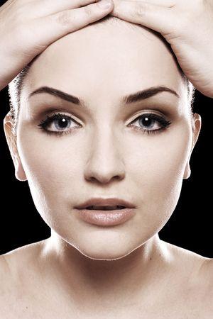 A close up di un bel giovane womans volto davanti a uno sfondo nero. Archivio Fotografico