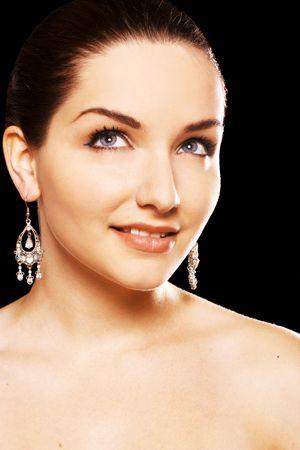 classy woman: A close up of a beautiful young woman wearing diamond earrings.