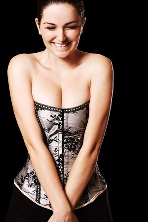 A pretty young woman wearing a corset and pushing her breasts together and laughing/smiling, in front of a black background. photo