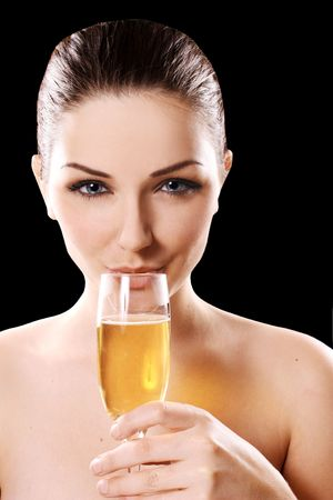 A pretty young woman drinking champagne in front of a black background. photo