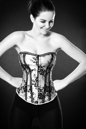 A pretty young woman wearing a corset and laughing/smiling, in front of a dark background. Stock Photo - 6227313