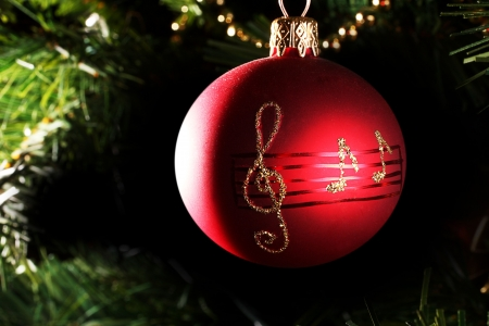 A close up di una pallina di Natale rosso con note musicali. Archivio Fotografico