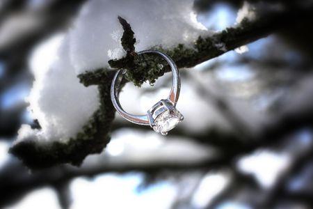 A beautiful diamond ring among a snowy outdoor scene. photo