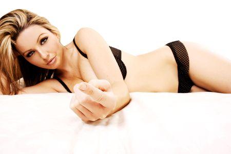 Una bella giovane donna sdraiata sul suo letto e che ti dice di venire a lei.