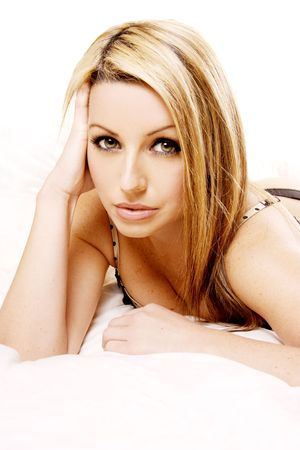 A beautiful young woman looking at the camera, lying on her white bed. photo