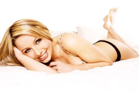 Una bella donna giovane sorridente sdraiata a letto nel suo intimo.