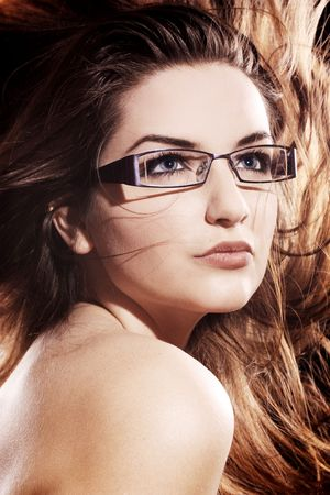 A beautiful young woman wearing fashionable glasses with her hair in motion. Stock Photo - 6535391
