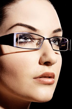 woman wearing glasses: A beautiful young woman wearing fashionable glasses in front of a black background.