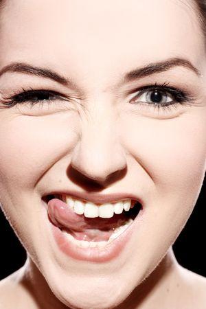 odontologia: A close up de una mujer joven tirando de una cara rid�cula.