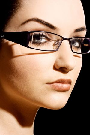 eye wear: A beautiful young woman wearing fashionable glasses in front of a black background.