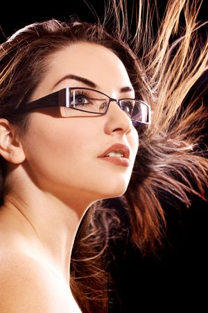 A beautiful young woman wearing fashionable glasses with her hair in motion. photo