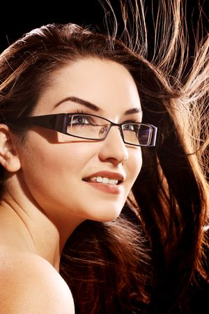 brown hair blue eyes: A beautiful young woman wearing fashionable glasses with her hair in motion.