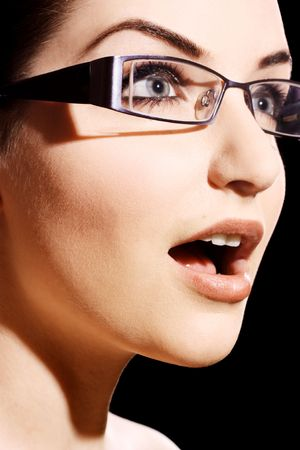 amazement: A beautiful young woman wearing fashionable glasses in front of a black background.