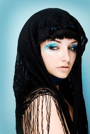 brown hair blue eyes: A close up of a beautiful young woman wearing sparkly make up and a head scarf.