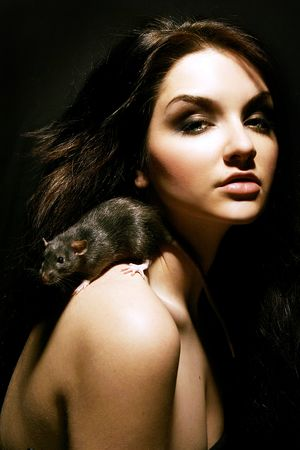 close up eyes: A beautiful young woman with a rat on her shoulder.