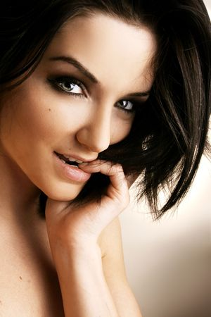 brown hair blue eyes: Close up of a beautiful woman in front of a neutral background.