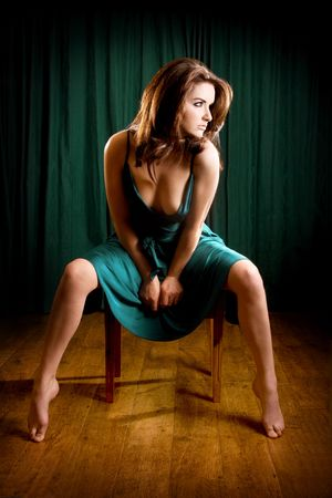 pointy: A glamorous young woman sitting on a stool and looking to the side. Stock Photo