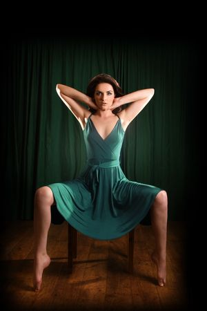 pointy: A glamorous young woman sitting on a stool and looking to the camera. Stock Photo