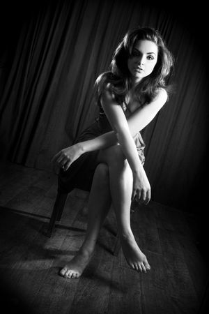 A glamorous young woman sitting on a stool and looking to the camera.. Stock Photo - 6902960