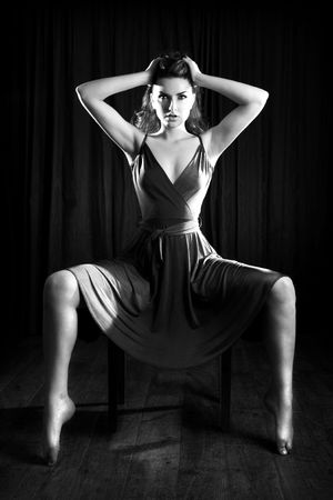 A glamorous young woman sitting on a stool and looking to the camera. Stock Photo - 7061474