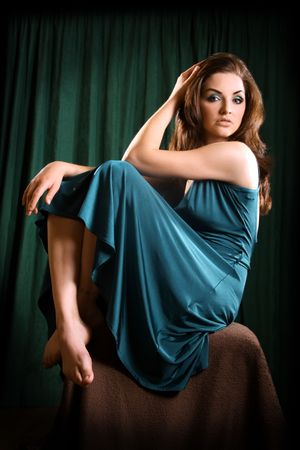 A glamorous young woman sitting on a stool and looking at the camera. photo