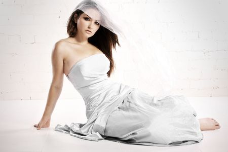 A pretty young woman in bridalwear in a white studio with wind in her hair.